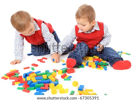 Cute caucasian twin brothers playing with bricks. All isolated on white background.