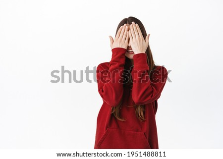 Cute caucasian woman in red hoodie covering her face and eyes with palms, smiling, waiting for surprise, playing peekaboo hide n seek, standing against white background Foto stock ©