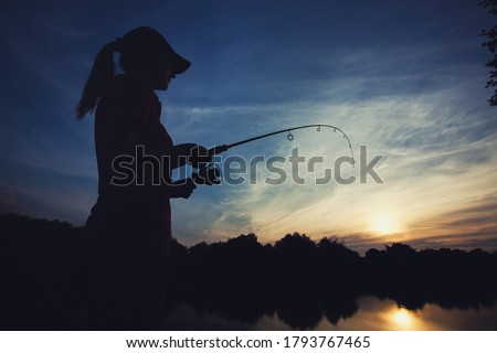 Cute caucasian woman is fishing with rod on the summer lake on the sunset