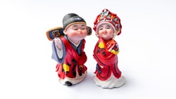 Cute ceramic figure with Chinese's traditional wedding costume clothes or dress. Concept of old fashion Asian bride and groom. Slightly defocused and close-up shot. Isolate on white background.