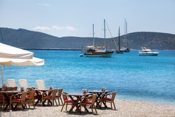 Cute chairs and table on the beach at seaside restaurant in Bodrum, Turkey
