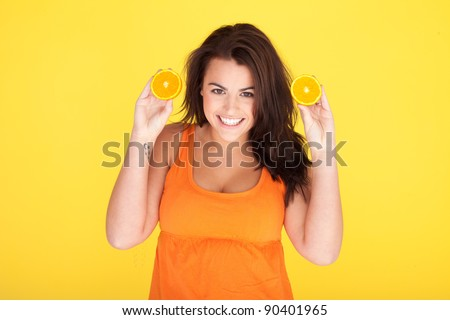 Cute Cheeky Woman Having Fun With Oranges, beautiful woman with cheeky smile holding up two orange slices, studio shot on orange.