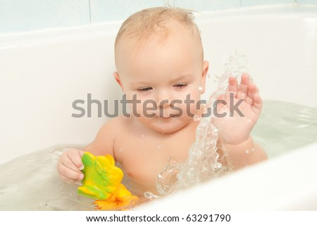 cute cheerful baby play in bath with toy. slapping on water