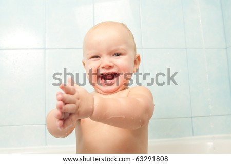 cute cheerful baby slapping on the water in bath