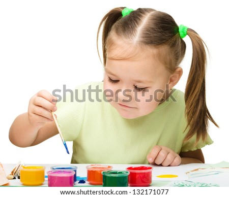 Cute cheerful child play with paints while sitting at table, isolated over white