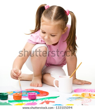 Cute cheerful child play with paints while sitting on floor, isolated over white
