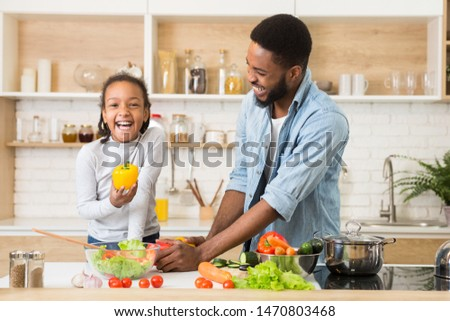 Cute Cheerful Girl Holding Pepper While Helping Dad Cooking Dinner In The Kitchen, free space