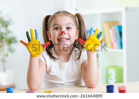 cute cheerful girl showing her painted hands in playroom