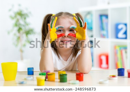 cute cheerful kid girl showing her hands painted in bright colors #248596873