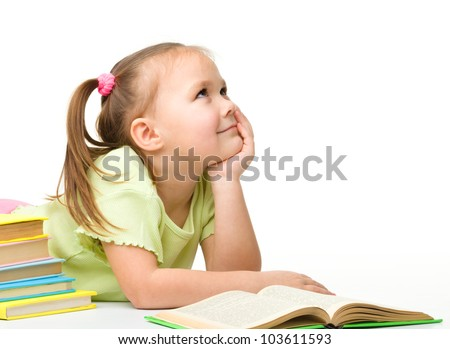 Cute cheerful little girl is dreaming while reading books, isolated over white