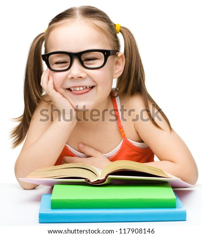 Cute cheerful little girl reading book while wearing glasses and sticking her tongue out, isolated over white