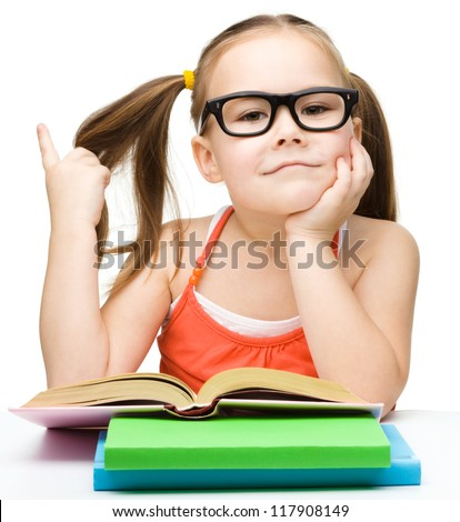Cute cheerful little girl reading book while wearing glasses and waving her hair, isolated over white