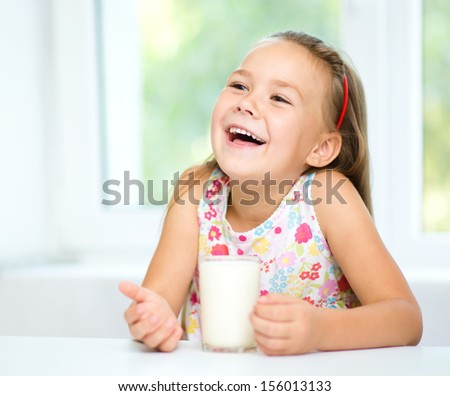 Cute cheerful little girl with a glass of milk - stock photo