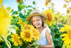 Cute child armful of sunflowers in summer field. Beautiful  child in light summer dress straw hat country life. Summer time concept.