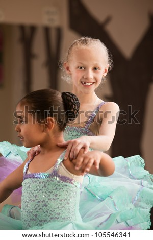 Cute child ballet student helps her partner during rehearsal