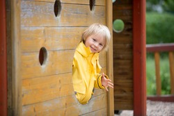 Cute child, blond boy, playing on playground on a cloudy day, springtime