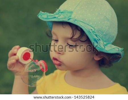 Cute child blowing big bubble. Closeup vintage portrait
