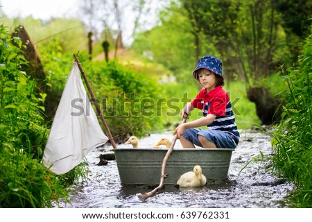 Cute child, boy, playing with boat and ducks on a little river, sailing and boating. Kid having fun, childhood happiness concept