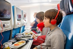 Cute child, boy, watching TV on board of aircraft, traveling on vacation with parent and siblings going for a summer holiday