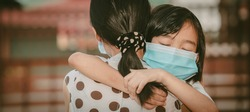 Cute child daughter hugging mother on blurred home background, kids school back to home on mather's day, Asian children and mother wearing mask protect coronavirus 19 and pm 2.5 particle in air