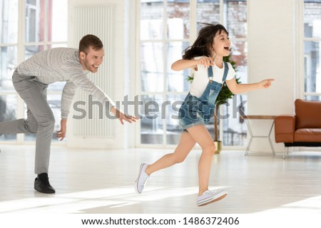 Photo of Cute child daughter running from happy dad catching playing tag and touch game at home, father chasing excited kid girl having fun enjoy leisure activity laughing spend time together in living room