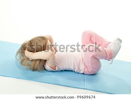 Cute child doing sport exercises on a training mat; white background