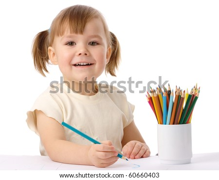 Cute child draws with color pencils, isolated over white - stock photo