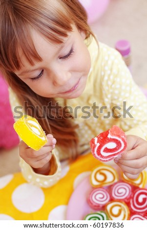 Cute child eating candies at home