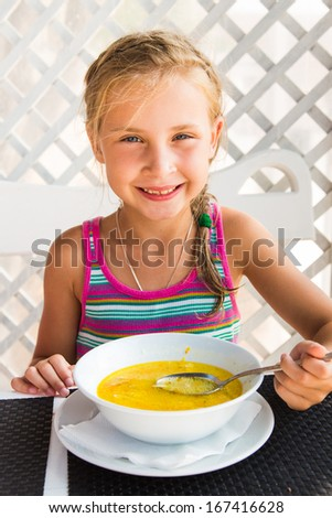 Cute child eating soup from the bowl, healthy food