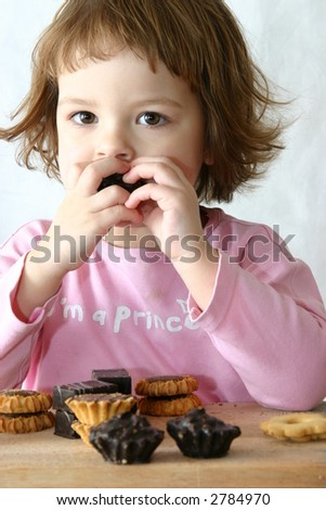 cute child eating tasty chocolate cookies on white
