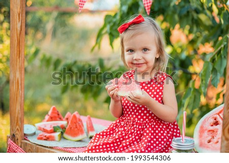Cute child eats ripe juicy watermelon at summertime. Child, baby, healthy food snack for children. Adorable little girl trying to sell lemonade. Watermelon lemonade with ice and mint