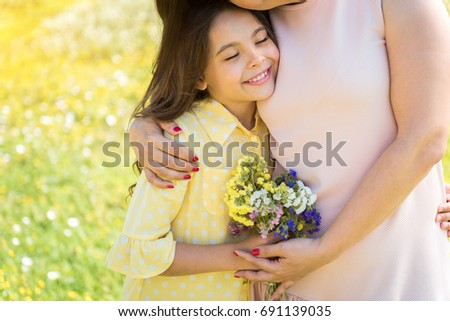 Cute child embracing with mother on grassland #691139035