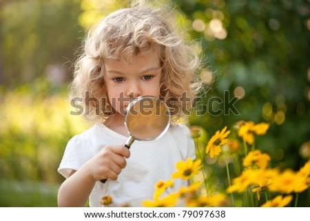 Cute child explorer flowers in garden - stock photo