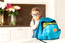 Cute child get ready for school at home sunny morning kitchen.Schoolgirl holds backpack for school day.Education,learning.Back to school.End of epidemic Coronavirus.Hello autumn