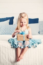 Cute Child Girl Opening Gift with Blue Ribbon at Home. Child with Gift Box