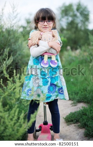 Cute child girl poses outdoors with baby doll and red scooter