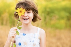 Cute child girl wear dress with sunflower in summer field. Happy little girl hide eye with sunflower. Summer time concept.