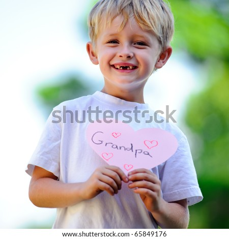 Cute child holds up a paper cut out of a heart with writing on it