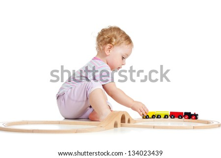 Cute child is playing with wooden train isolated on white - stock photo