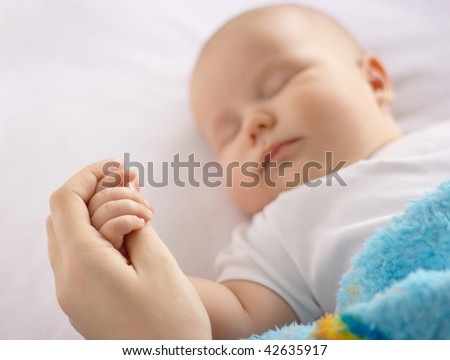 Cute child is sleeping in bed holding mother's hand, focus on hand