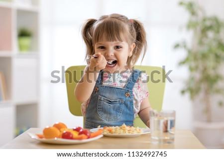 Cute child little girl eating healthy food in kindergarten