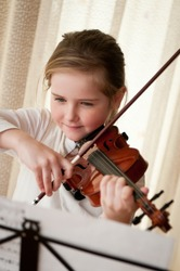 Cute child (little girl) playing violin and exercising at home