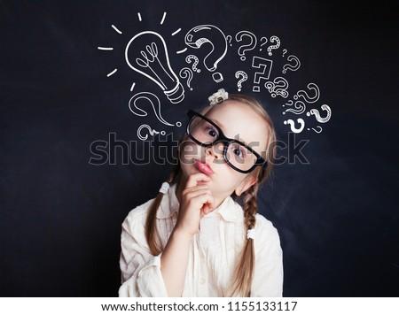 Cute child little girl with chalk lightbulb new idea symbol . Kid ideas and brainstorm Stock photo ©