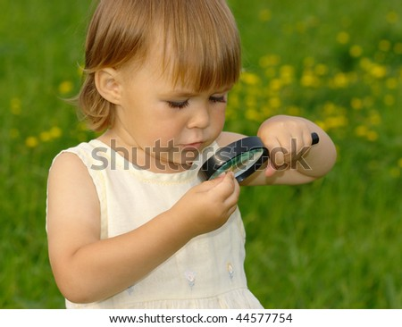 Cute child looking at little snail through magnifying glass