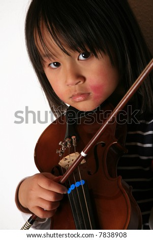 cute child looking at the camera with a violin in hands
