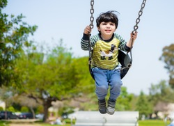 Cute child on swinging set in the playground
