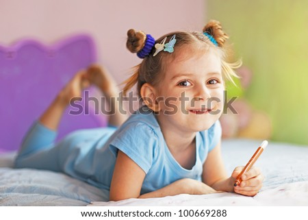 Cute child  painting in her nursery at home