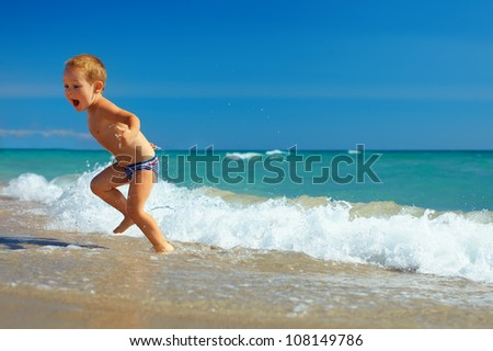 cute child running from sea  waves on beach
