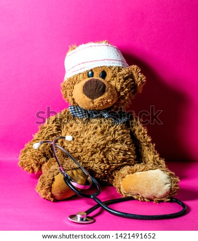 cute child's teddy bear with a head bandage and stethoscope for concept of domestic mishap and hospital treatment over nursing pink background  #1421491652