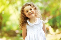 Cute child shone with happiness, curly hair, charming smile